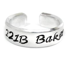 Brainy is the new sexy, and no one is sexier than everyone's favorite detective. This bright aluminum ring has been hand-stamped with 221B Baker Street in our Calligraphy font, with a little keyhole d