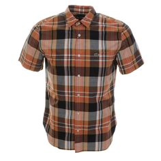 Lacoste Short Sleeved Cotton Checked Shirt In Brown And Indigo Dark Blue, Regular Fit. An overall large checked design to the fabric in brown, white and blue with a full front pearlescent button opening with a pointed shirt collar and short sleeves. A pouch pocket on the left of the chest featuring the small signature embroidered Lacoste Crocodile logo in green, red, black and white. The reverse features a central pleat complete with a curved hem design. 100% Cotton. Brand New Fantastic…