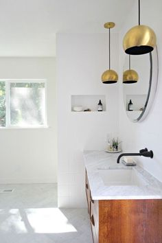 Brass and Black fixtures are so bold in this all white bathroom. Love the floating walnut vanity