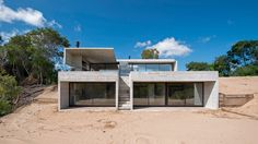 Luciano Kruk Arquitectos has stepped this board-marked concrete summer house down a sandy dune in a coastal town near Buenos Aires, to offer views of acacias and a pine forest beyond.
