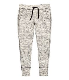 CONSCIOUS. Jogger-style pants in melange organic cotton jersey with a fine-knit look. Decorative overlock stitching, elasticized drawstring waistband, side pockets, and tapered legs with wide ribbing at hems.
