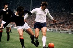 England's Martin Chivers (right) holds off Scotland's Bobby Moncur (centre), watched by Scotland's John Greig in 1971.