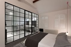 Rather than a solid dividing wall a glass wall stops from making the bedroom divided to fit an ensuite from feeling small!!
