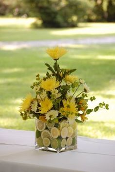 This is a great idea to add color, sliced lemons in the glass vase for your flower arrangements
