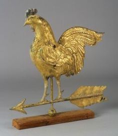 Molded and Gilded Copper and Zinc Rooster Weathervane, America, late 19th century, full-body rooster with detailed feathers and sheet copper tail, zinc feet, red painted comb and wattle, mounted on an arrow above a small sphere, including wooden stand, (wear, a couple of bullet dents), ht. 26 7/8, lg. 26 in.  Sold for $ 5,288