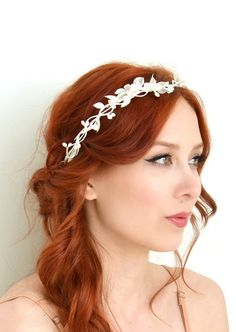 Whisper of spring This pretty little crown features a base of white berry branches, leafy garlands, and a small cluster of sheer chiffon