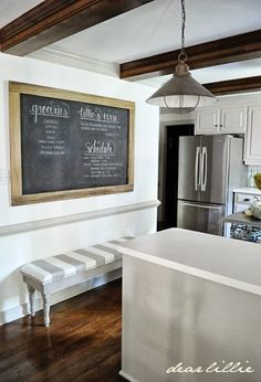 An Oversized Chalkboard And Bench In The Kitchen.