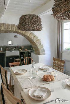 Salle à manger et cuisine séparées par un arc en pierre, assiettes et suspensions 'Athezza', lin naturel boutique 'Blanc Cassé' à Uzès