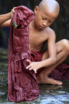 Self sufficient, this young monk of Myanmar wash his clothes with soap by himslef.
