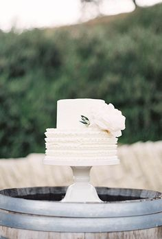 Brides.com A two-tiered white wedding cake with a ruffled layer and flower detail, created by Enjoy Cupcakes. Photo: Jen Huang Photography