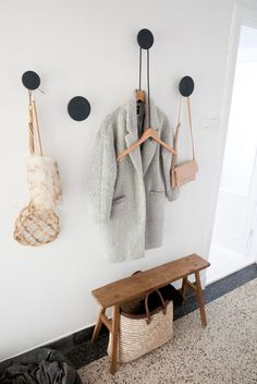 Drill a hole, add dowel and long screw (don't screw all the way in). Hot-glue wooden disk to the screw. Add a couple of wooden coat hangers = fancy coat and bag storage for the hallway. Done!: