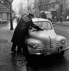 """Paris 1960 Photo: Robert Doisneau. """"Oh dit vertrouwde beeld van de licht gebogen agent, die de bekeuring onder je ruitenwisser schuift! Nu is alles digitaal""""."""