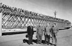 "A new type of roof was demonstrated at Behlen Manufacturing Co. in Columbus, Nebraska, on Oct. 15, 1959. To illustrate its strength, 279 Behlen employees stand on a test section. In the foreground are, from left, Walter Behlen, president; his father, Fred E. Behlen; and brothers Gilbert E. Behlen and H.P. ""Mike"" Behlen. THE WORLD-HERALD"
