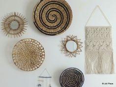 Une accumulation de paniers ronds, miroirs en rotin et tissages en macramé sur un mur