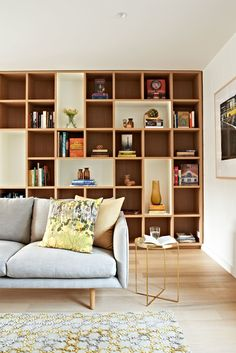 This grey living room with floor to ceiling bookcases uses a very ...