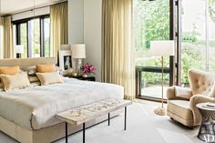 Thomas O'Brien designed the bed in the master suite, upholstering the headboard in a Donghia fabric and using a Christopher Farr Cloth textile for the coverlet. At the foot of the bed is a vintage André Borderie table, while the circa-1945 armchair is attributed to Mogens Lassen; the '60s French floor lamp is from ReGeneration | White, cream, taupe, gold, black.