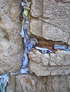 Papers with prayers and wishes that have been inserted into the cracks between the stones of the ancient Western Wall in Jerusalem, Israel