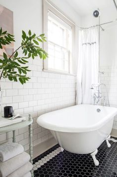 """After: The brand-new gleaming white tub (they had to remove the feet to get it through the closet-size door). The Lulie Wallace nude is a prized piece of art. """"I always wanted to get a nude painting and then we finally found one that felt tasteful,"""" Adam says."""