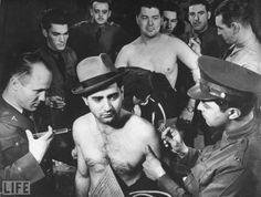 On this day in 1942, Congress approves a bill to lower the draft age to 18 and raising the upper age limit to 37.  In 1940, America launched its first peacetime draft in the history of the country. This highly charged George Strock photograph of inductees at Fort Dix, New Jersey — including the central figure still donning his own hat, a last vestige of civilian individuality amid the impersonal-cattle-call atmosphere of innoculations, pokings, proddings, and exams — speaks to a count