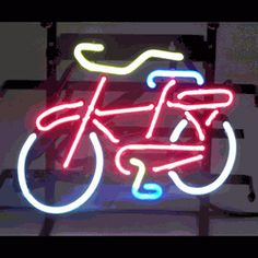 "BICYCLE NEON SIGN-NN5BICYL  12"" wide, 11""high, 4"" deep  When it comes to transportation, you're a pedal power person! Show it with our Bicycle Neon Sign, featuring multi-colored, hand blown tubing supported on a black, finished metal grid. The Bicycle Neon Sign can be displayed flat on a wall or in a window or alternately be placed upon a shelf."