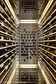 ♂ A mirrored wine cellar creates an illusion of infinate depth. Interior designed by Andee Hess of Osmose.
