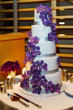 This five tiered cake is adorned with sleek silver ribbon and dripping with purple sugar orchids.