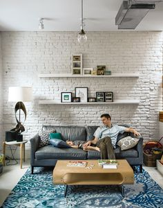 white brick wall + floating shelves + blue rug
