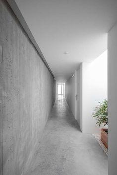 Concrete and plaster corridor. Pe No Monte Rural Trousim by [i]da Arquitectos.