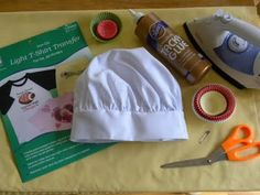 Baking hats (of course!  I ordered mine from KNG.com), standard size baking cups (white and any other colors you may like), mini baking cups, iron-on transfer paper, an iron, glue, scissors and large safety pins.