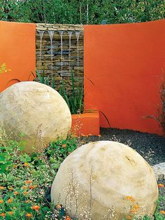 Colorful Wall Helps to Highlight Garden Sculptures Brightly painted wall helps to accentuate the large concrete sculptures that are part of this garden design.