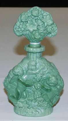 A Czechoslovakian Glass Perfume Bottle,having a floral finial over the baluster form body with putti in relief.Height 6 1/2 inches.