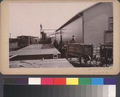 The California Wine Association winery in Geyserville, California, with a wagon full of grapes approaching the loading dock, circa 1890s.