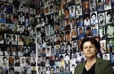 A Bosnian Muslim woman from Srebrenica, sitting under pictures of victims of the genocide in the town during the 1992-1995 Bosnian war, watches the television broadcast of Ratko Mladic's court proceedings, in Tuzla, on June 3, 2011. Former Bosnian Serb military commander Mladic said he defended his people and his country in the Bosnia war and now intended to defend himself against war crimes charges at the U.N.'s Yugoslavia tribunal. Mladic was indicted over the 43-month siege of the Bosnian…