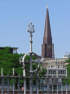 011_17378 - Eisenzaun, der die ehem. Zollgrenze am Hamburger Freihafen bildet; ein Dreizack ist als Dekorelement an der Zaunspitze angebracht. Im Hintergrund der Fotografie Kirchturm der Hamburger Hauptkirche St. Jakobi.