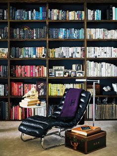 Color-coded bookshelves; vintage black leather recliner; Wilde found the purple HERMÈS blanket on eBay; vintage LOUIS VUITTON luggage belonged to French film actress Michèle Morgan and came with a 1930s straw boater hat inside.