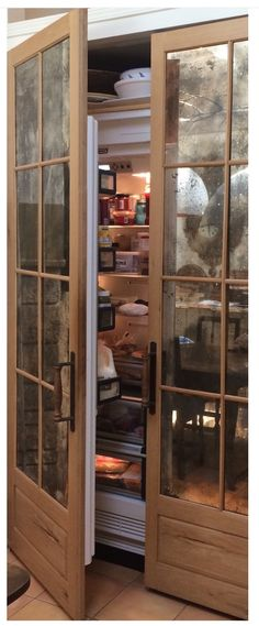 Refrigerator door refaced with a pair of French doors and antique glass.