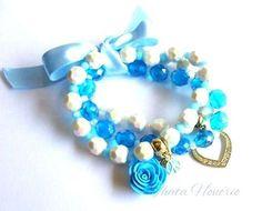 Cód: PUL331    Conjunto com 3 pulseiras de pérolas, pedras de vidro azul, pingentes diversos e fita de cetim. R$ 14,00