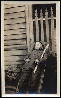 Post mortem. Boy outside house. circa 1900.