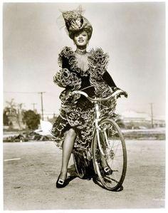 Marlene Dietrich rides a bike.