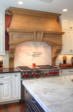 Cast stone range hood. Custom Maple cabinetry. Remodeling by Martin Bros. Contracting, Inc