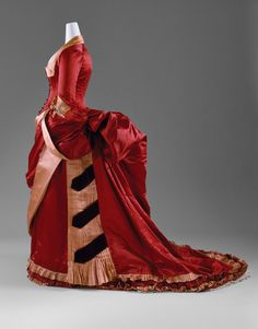 Evening Dress, 1884–86. American or European. The Metropolitan Museum of Art, New York. Gift of Mrs. J. Randall Creel IV, 1963 (C.I.63.23.3a, b) | The bustle, which took hold in the 1870s, was at its most exaggerated extension by 1885. At its extreme, it was almost perpendicular to the small of the back. It was a popular conceit that the cantilevers of these bustles could support an entire tea service. #OneMetManyWorlds