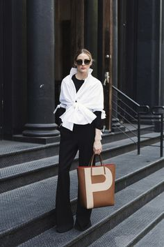 Olivia Palermo street style: white knotted blouse, wide legged pants, sweater, initials leather tote bag