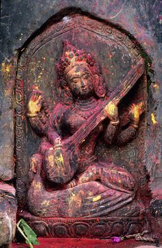 'Saraswati, goddess of learning.'Relief of Saraswati, the Goddess of Learning, at a small temple near Lele, south of Patan. All those who worship her are believed to receive wisdom and learning. As goddess of music and poetry she is revered alike by Hindus and Buddhist. She is holding and playing Bina with her two hands and in her other left hand she holds a copy of the vedas. Her mount is a peacock. Yellow and red powder has been smeared on the sculpture during puja offerings. Photo Paul…