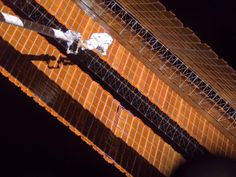 Astronaut Scott Parazynski moves toward a tear in one of the space station's solar array blankets in 2007. He is attached to the end of the Orbiter Boom Sensor System, or OBSS.