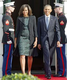 Michelle Obama wore a jade green printed Tanya Taylor dress and a light black coat to meet the Canadian Prime Minister.