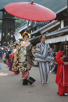 A woman dressed as tayu along with lesser ranking prostitutes, a kamuro and an attendant during a parade.
