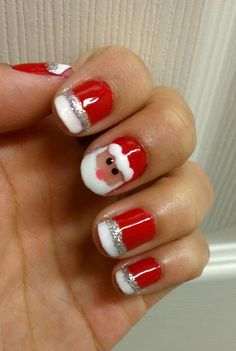 Very cute Santa nail art. Paint an adorable Santa head amidst the Santa hats in your nails. You can use silver glitter for the lining of the hats.