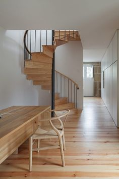 Light, open, airy hallway and spiral staircase with light colored wood.  Feitais House by José Lobo Almeida