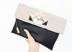 ATTENTION pochette réalité sur commande 10 jours de délai Grande pochette main en simili cuir noir et lin, rehaussé dapplications paillettes. La pochette peut être à la fois un sac main et une pochette à glisser dans un sac. La pochette est zippée et doublée coton, elle se plie en deux et est maintenue par un aimant. couleur noir et jaune 32cm /23cm refermée.