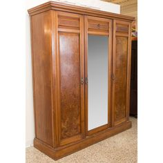 Exceptional antique English knockdown wardrobe with a spacious interior. Features hanging rods and shelves behind the two outer doors; three drawers, three sliding shelves, and a fixed shelf in the center; and an exterior full-length mirror. Accentuated with birdseye maple veneers, crown molding, and decorative carvings. A solid antique find in wonderful condition.